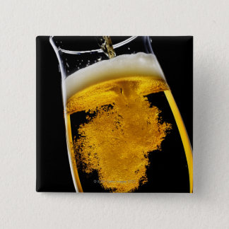Beer been poured into glass, studio shot pinback button