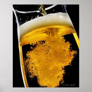 Beer been poured into glass, studio shot poster
