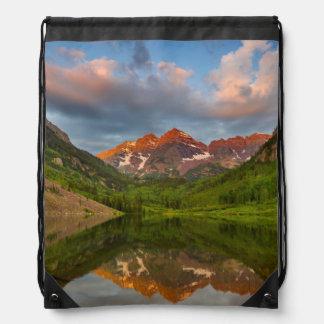 Belces marrón reflejan en el lago marrón tranquilo mochila
