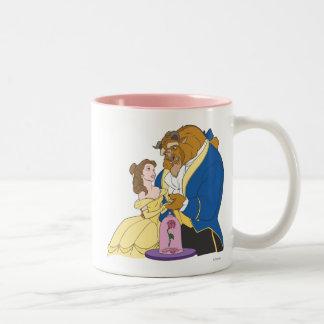 Belleza y bestia que llevan a cabo las manos taza de café de dos colores