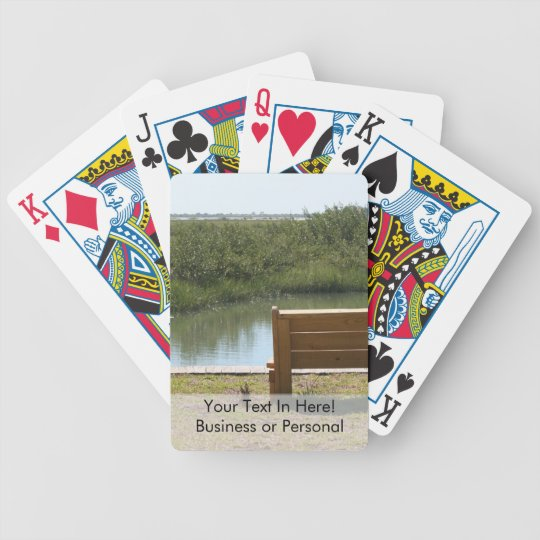 Bench by river with grass and water bicycle playing cards