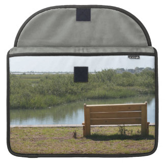 Bench by river with grass and water sleeves for MacBooks