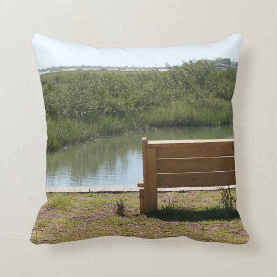 Bench by river with grass and water throw pillow