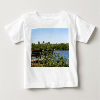 Bench on dock with nature preserve blue sky baby T-Shirt