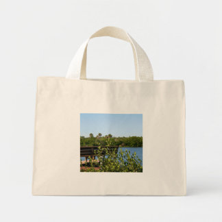 Bench on dock with nature preserve blue sky canvas bags