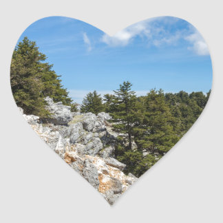 Bench on rocky mountain with trees and blue sky heart sticker