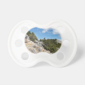 Bench on rocky mountain with trees and blue sky pacifier