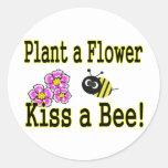 Bese una abeja con las flores rosadas pegatina redonda