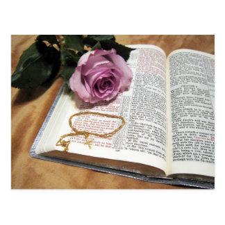 Biblia y color de rosa púrpura con la cadena postal