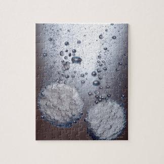 Bicarbonato de tabletas de la soda en agua rompecabeza