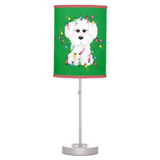 Bichon Frise con la lámpara de mesa de las luces d