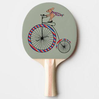 Bici pasada de moda que monta del perro en la pala de tenis de mesa