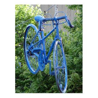 Bici que cuelga sobre la calle tarjeta postal