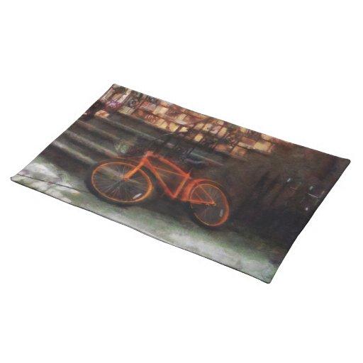 Bicicleta anaranjada por la arenisca de color oscu manteles