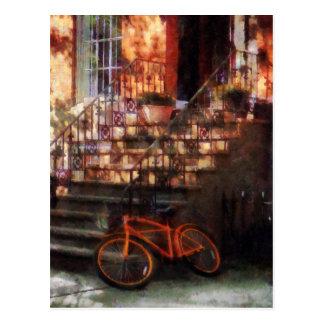 Bicicleta anaranjada por la arenisca de color oscu postal