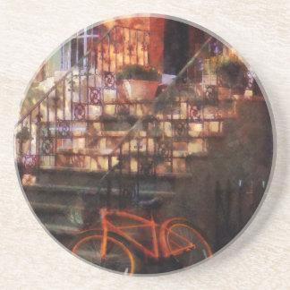 Bicicleta anaranjada por la arenisca de color posavasos cerveza