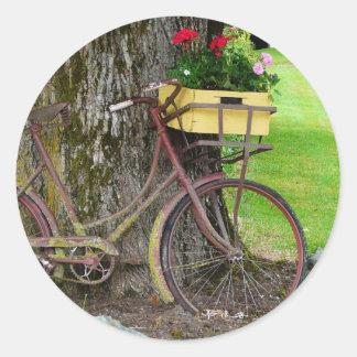 Bicicleta antigua vieja con la cesta de la flor etiquetas redondas