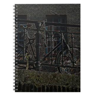 Bicicleta de neón contra la verja libros de apuntes con espiral