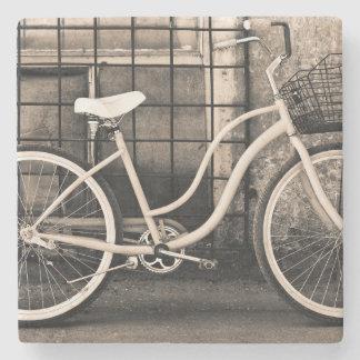 Bicicleta del vintage con la cesta posavasos de piedra