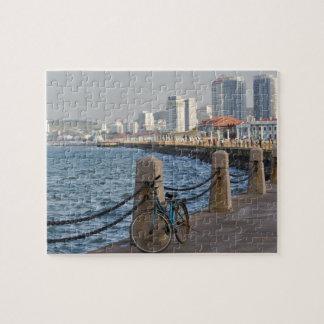 Bicicleta en la costa con horizonte de la ciudad d rompecabezas