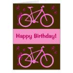 Bicicleta en tarjeta rosada del feliz cumpleaños