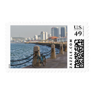 Bicycle at waterfront with Yantai city skyline, Postage