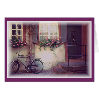 BICYCLE PROPPED AGAINST HOUSE WITH FLOWER BOXES & CARD