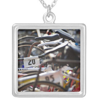 Bicycles on the rack at a triathlon race ready square pendant necklace