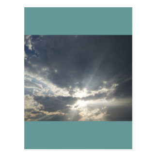 Big rays of light with many clouds and blue sky postcard