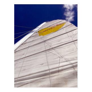 big white sail on deep blue sky background postcard