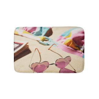 Bikini Top And Heart Shape Sunglasses On Beach Bath Mat