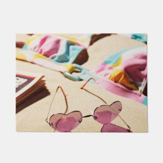 Bikini Top And Heart Shape Sunglasses On Beach Doormat