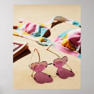 Bikini Top And Heart Shape Sunglasses On Beach Poster