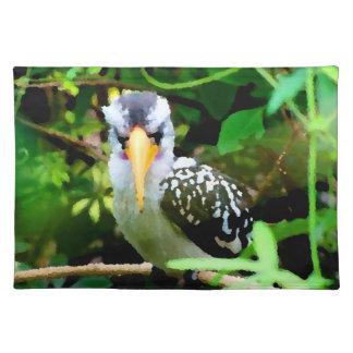 bird black white yellow beak against green painted placemat