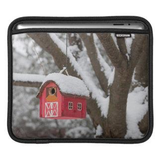 Bird house on tree in winter iPad sleeves