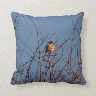 Bird in bare branches against blue sky pillow