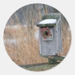 Bird, nest box with holiday wreath in winter round stickers