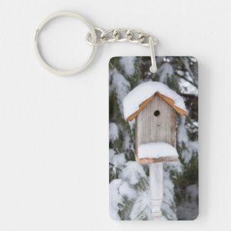 Birdhouse near pine tree in winter rectangular acrylic key chains