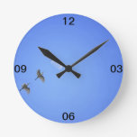 Birds flying to moon in blue sky round wall clocks