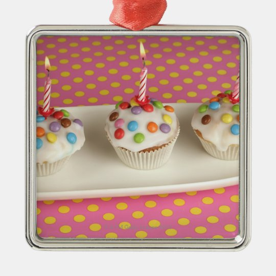 Birthday muffins with icing, sprinkles and metal ornament