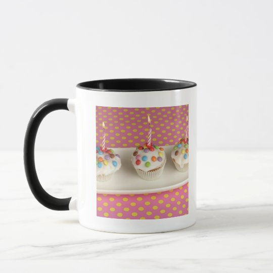 Birthday muffins with icing, sprinkles and mug