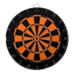 black and orange dartboard with darts