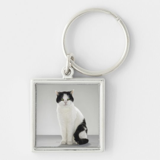Black and white cat with glowing green eyes keychain