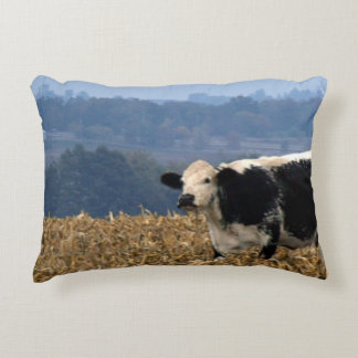Black and White Cow grazes in freshly plowed field Decorative Pillow