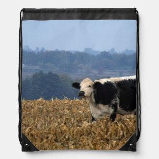 Black and White Cow grazes in freshly plowed field Drawstring Bag