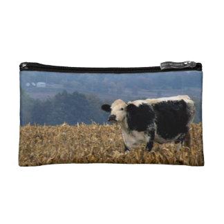 Black and White Cow grazes in freshly plowed field Makeup Bag