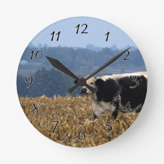 Black and White Cow grazes in freshly plowed field Round Clock