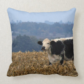 Black and White Cow grazes in freshly plowed field Throw Pillow