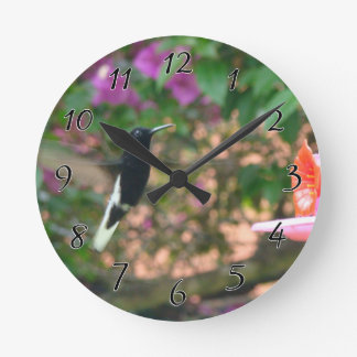 Black and White hummingbird flying at a feeder Round Clock