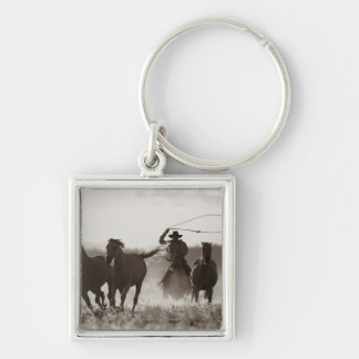 Black and White photo of a Cowboy Lassoing Horses Keychain
